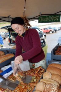 Rena Loebker of Crumbs Bakery, a regular at the Athens Farmers Market, serves pizza topped with vegetables purchased from the market.